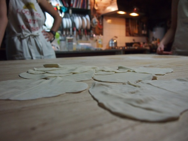 """Zurück in der Küche fängt die """"Arbeit"""" an: Wir lernen die richtige und exakte Zubereitung des Teigs für die Empanadas, den wir sanft kneten und für die Füllung ausrollen."""