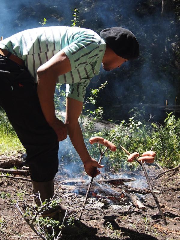 """Mitten im Wald machen wir Mittagspause: Hier bereitet Facundo unser Mittagessen, gewürzte """"Salchichas"""" auf dem Holzspieß, für uns zu."""