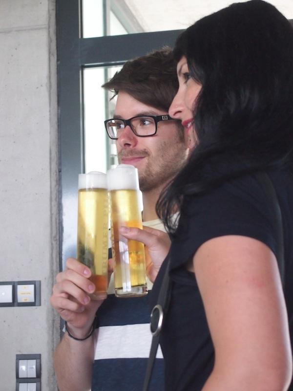 """Johannes von JustTravelous und Susi Maier vom Reiseblog """"BlackDotsWhiteSpots"""" genießen ein ausgezeichnetes Trumer Pils an der Zapfwand der modernen Brauerei."""