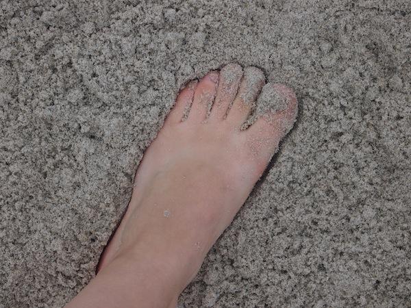 ... stecken Zehen in den Sand ...