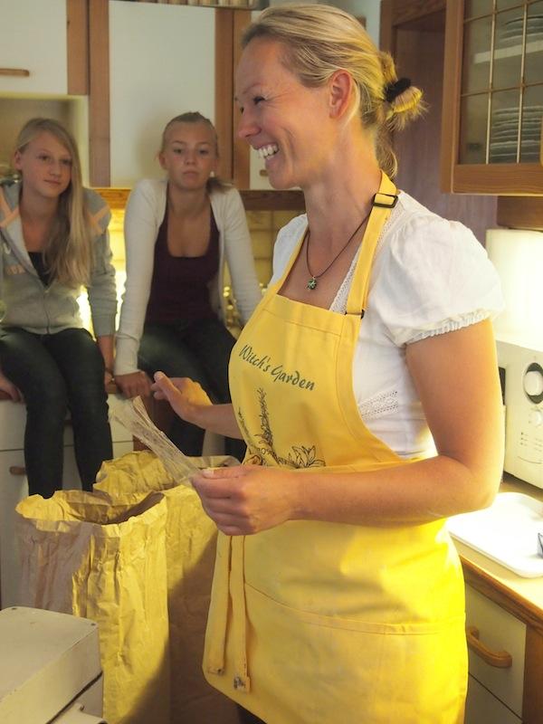 """Kathi mit ihrer Schürze """"Witch's Garden"""" empfängt uns im traditionellen Bauernhaus zum Brotbacken."""
