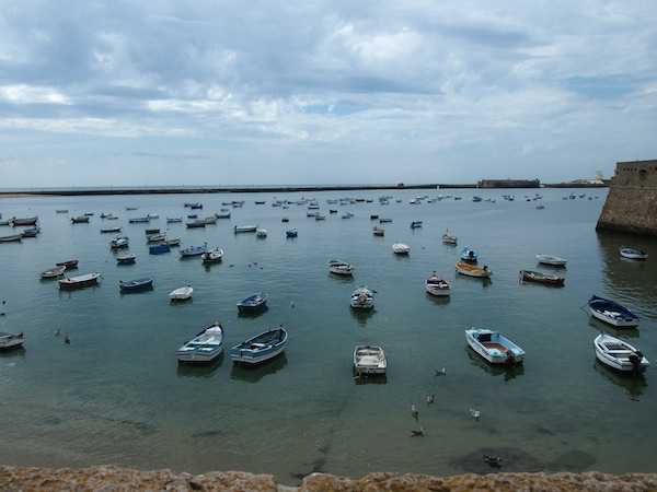 """Am Strand von La Caleta, dem berühmten """"Hausstrand"""" der Einwohner von Cadiz, tummeln sich diese zahlreichen Fischerboote."""