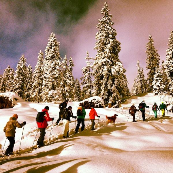 """... unser erfahrener Bergführer Matthias führt uns gerne """"quer-schnee-ein"""" durch den tief verschneiten Wald: Dank überdimensionaler """"Schneeschuhe"""", die direkt an die Winterschuhe montiert werden, sinken wir nicht ein und können buchstäblich überallhin stapfen."""