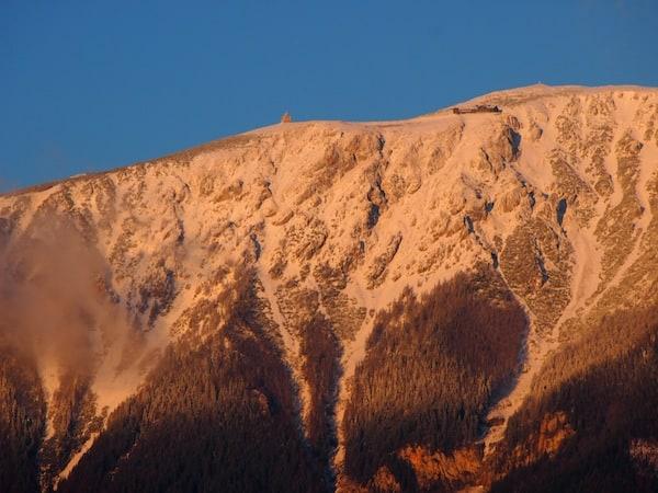 ... im Zentrum natürlich der mächtige Schneeberg mit der höchst gelegenen Bergkirche Niederösterreichs, auf fast 1.800 Metern Seehöhe sowie dem Bergbahnhof der Schneebergbahn, hier im Licht der Morgenröte gut zu erkennen.