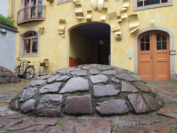 """Ankommen in der Kunsthofpassage (ein Schild weist an der Hauptstraße auf die hier in den Innenhöfen der Wohnhäuser verborgenen """"Kunstschätze"""" hin."""