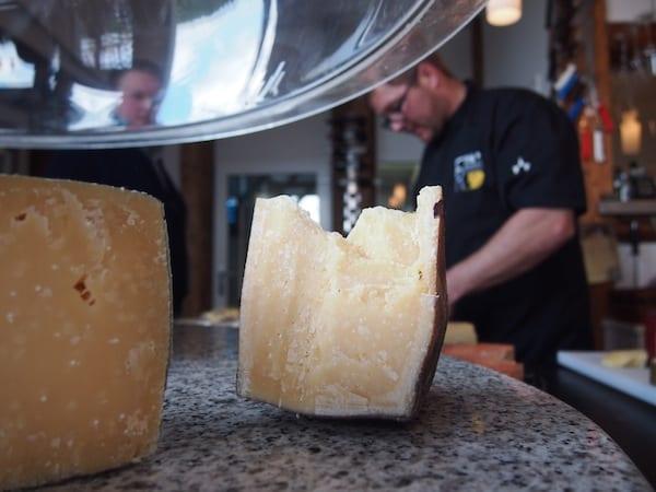 """Bernhard Gruber in Aktion: Wir lüften die Käseglocke, welche gleich am Eingang zu seinem Betrieb hängt, und sind erfasst vom immensen Duft verschiedener Käsesorten. """"An das Betriebsklima gewöhnt man sich mit der Zeit"""", meint er schmunzelnd."""