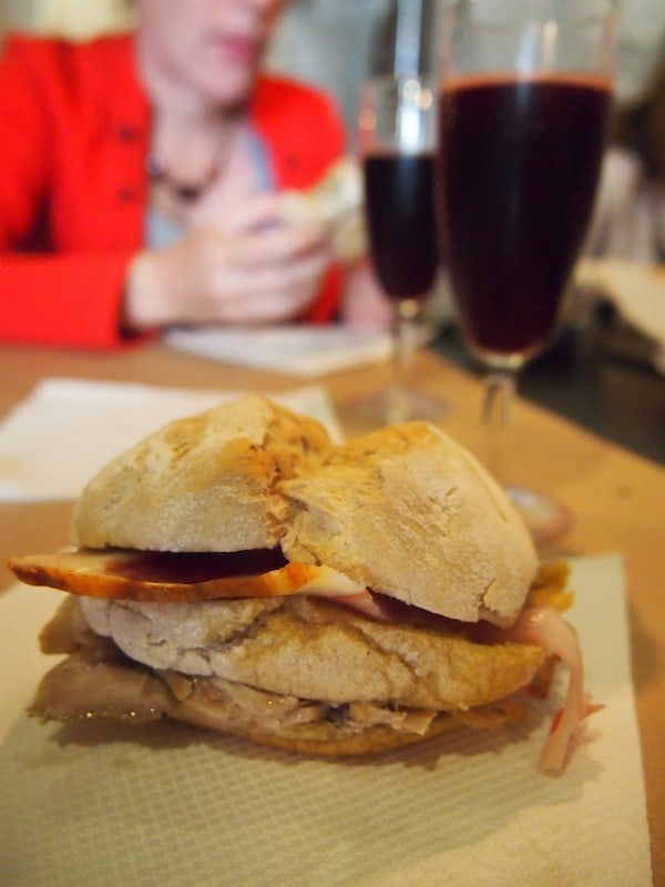 Hier genießen wir ein einzigartiges Sandwich, gefüllt mit köstlich duftendem Fleisch und Speck, dazu ein Glas prickelnden Rotweins ...