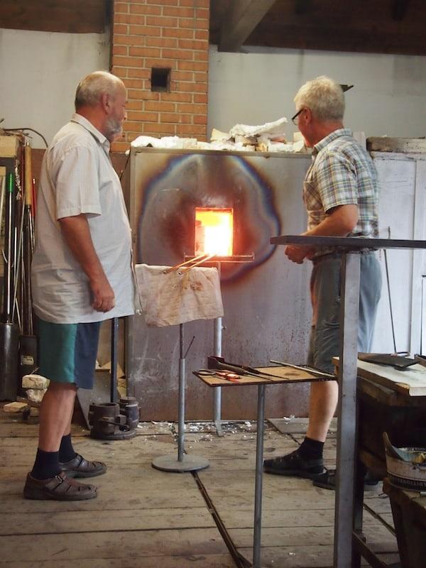 """Sicherheitsabstand ist hier gewährleistet: Im Herzen der Glashütte entnimmt der Glasbläser aus der über 1.000 °C heißen """"Glasmasse"""" aus Sand & Feuer die exakt richtige Menge, um verschiedene Erzeugnisse zu formen ..."""
