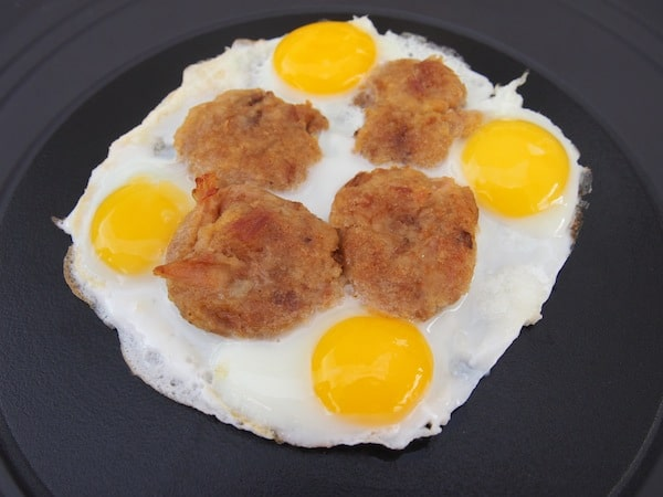"Continuing the ""gourmandises"" being served: Cut slices of Alheira sausages with fried eggs are simply delightful."