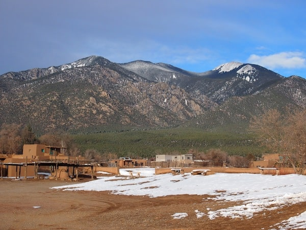 Taos Pueblo has been settled by Pueblo Indians some estimated 1.000 years ago, at the foothills of these sacred Pueblo mountains in the background, about one and a half hours north of the city of Santa Fe.