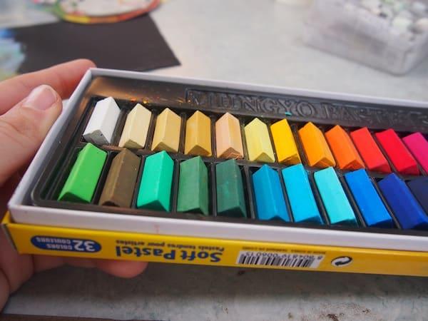 """Gleich zu Beginn schenkt sie uns dieses Set an Pastellfarben: """"Ihr könnt es gerne behalten und ich ermutige Euch, zuhause weiter zu machen: Ihr werdet sehen, das Malen mit Pastell beflügelt!"""", lächelt sie uns aufmunternd an."""