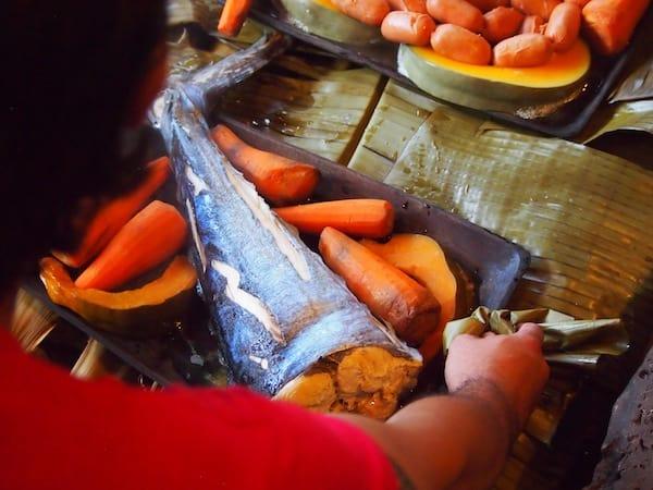 ... aus dem traditionellen Erdofen gehoben wird: Leckere Süßkartoffel & Fisch ...