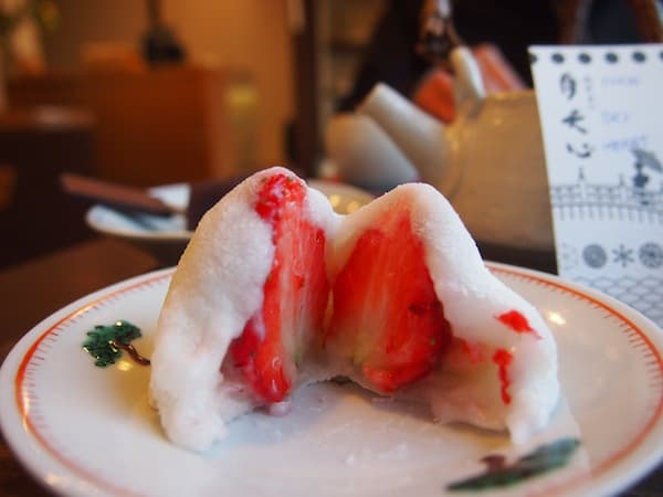 "Breakfast in Japan, however, can also be ""sweet & simple"": Here I am in Kanazawa's peaceful old town district, at a place called Moon.Sky.Heart, enjoying a secret rice dumpling unveiling a sweet strawberry fruit inside … delicious – OGISHI, I learn to say in Japanese!"