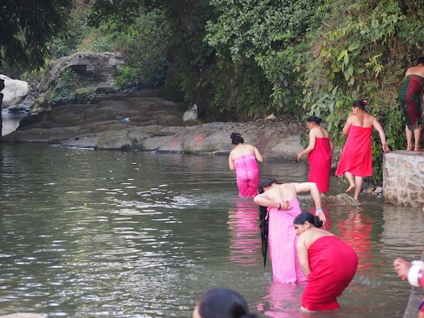 ... draws the crowds and many religious believers, including these women taking their ritual baths in the local river Sali ...