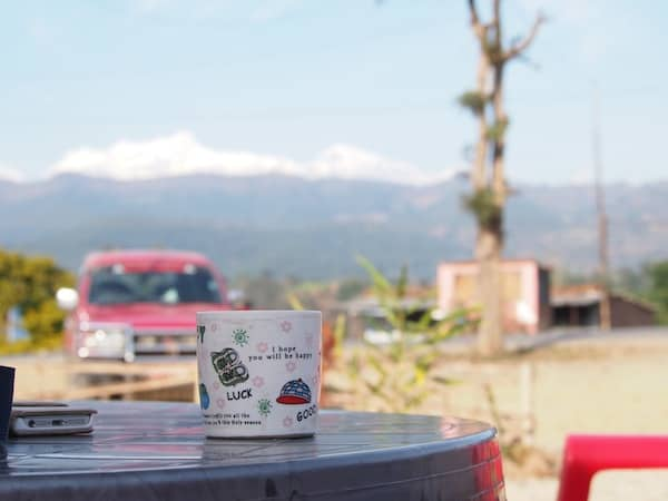Time for a coffee break by the road: Lucky travellers with a view of Rakesh' Jeep (much needed in later road conditions, as we would find!) and the mountains beyond.