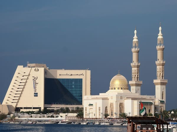 Modern-day culture in Sharjah greets us to a fusion of many worlds, as exemplified by this five star Radisson Blu Hotel against one of the many beautiful Mosques around here next to it.