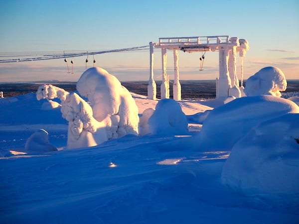 Tief verschneit strecken sich unter diesen bizarren Schneeskulpturen zähe Bäume der Abendsonne in Lappland entgegen.