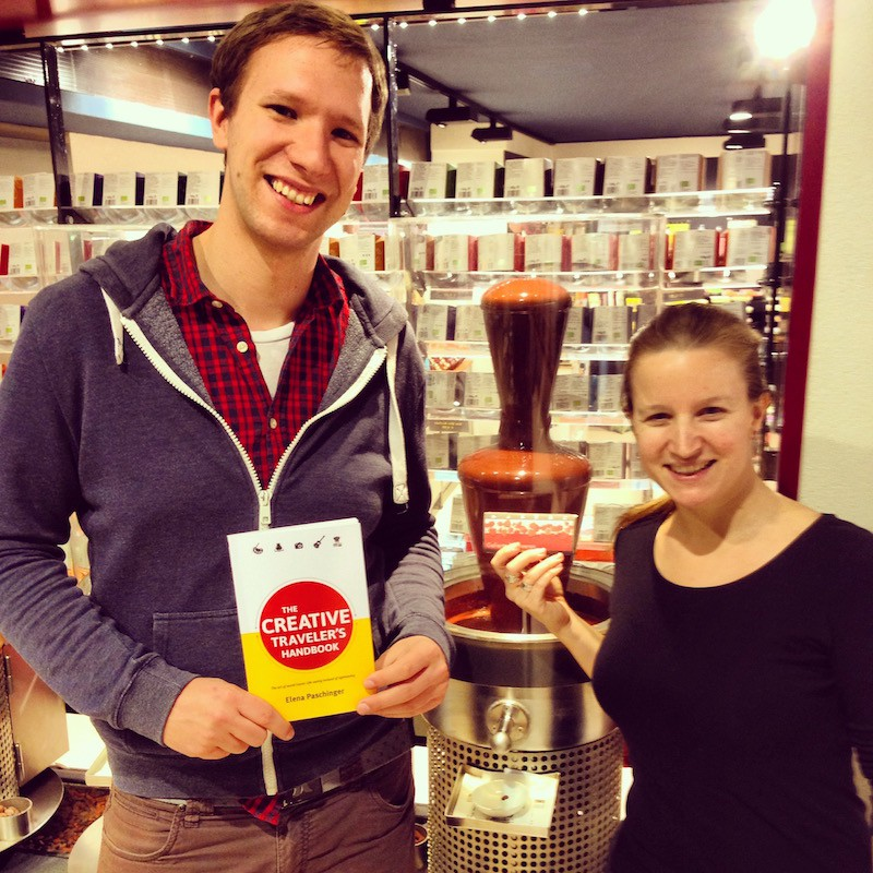 "Florian Figl, happily holding ""The Creative Traveler's Handbook"" in hand while meeting at the chocolate factory where he works (can you see the chocolate fountain in the back?)!"