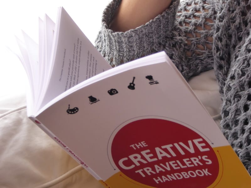 """Nicole Biarnes beim Lesen meines Buches, """"The Creative Traveler's Handbook"""" auf ihrer gemütlichen Wohnzimmer-Couch in Barcelona."""