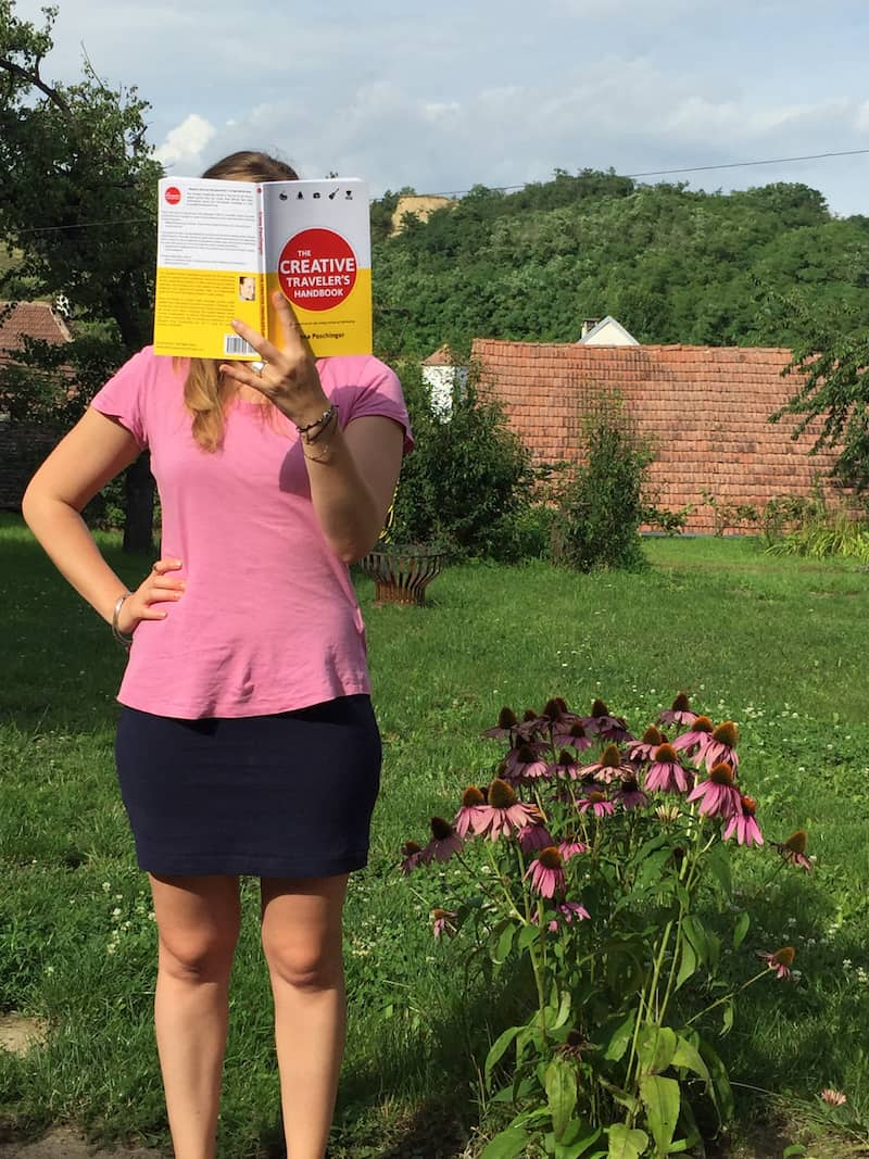 """Lucia Täubler & """"The Creative Traveler's Handbook"""" bei der sommerlichen Lektüre im Garten."""