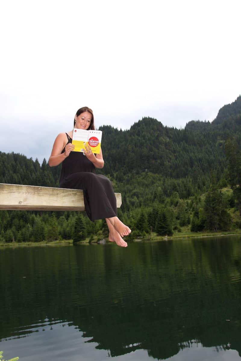 """Christina mit meinem Buch, """"The Creative Traveler's Handbook"""", an einem ihrer Lieblingsseen in Tirol."""