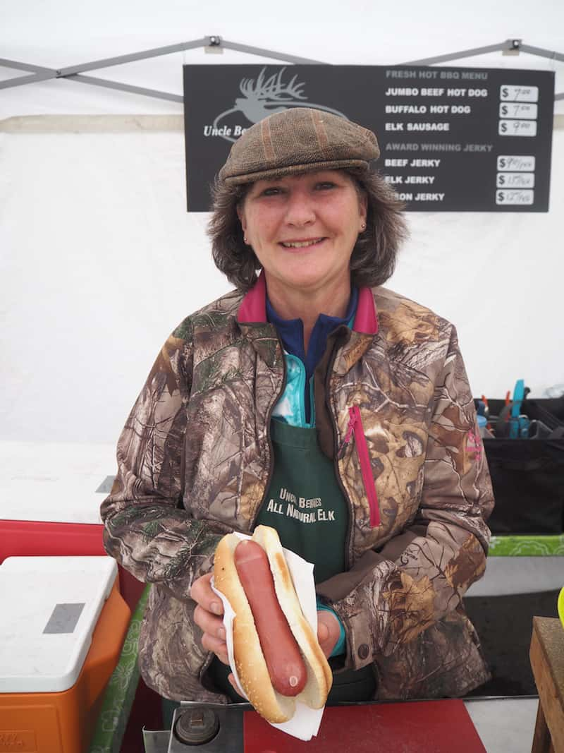 "For lunch, I can recommend heading across the street (yes, it really is all that close!) to the local Farmers' Market, where this lady is offering me a ""hot elk"" with meat from her hand-raised, farmed elk near Calgary!"
