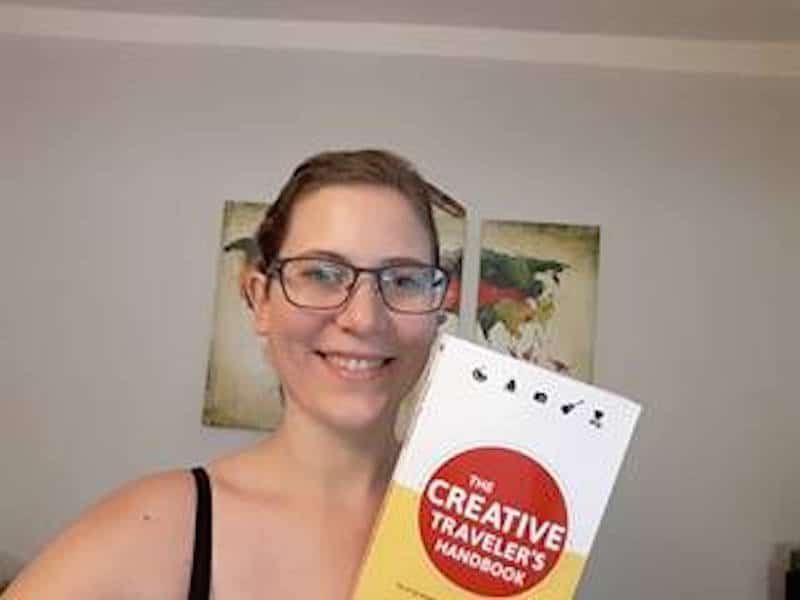 "Tina in her home country Burgenland, proudly holding up her copy of ""The Creative Traveler's Handbook""."