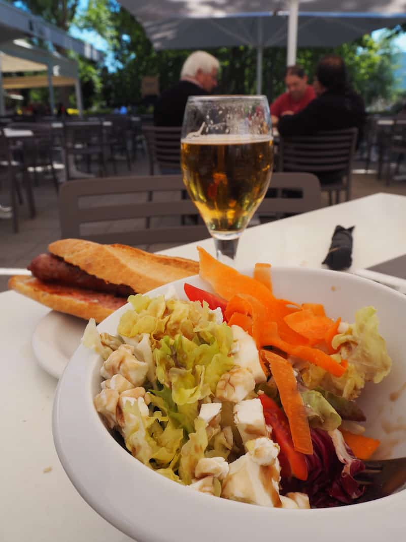 """Vora l'Estany"" in Banyoles : It's actually a restaurant, but this time, I just came here for these lovely tapas - a simple salad and a home-made sausage hot dog with a beer, which cost me no more than €8,- .. perfect and right by the lake, to come back to anytime !!"