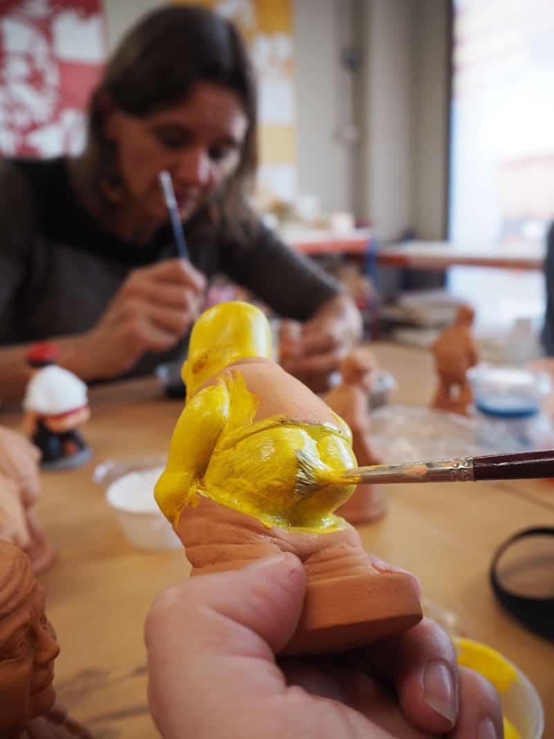 Der kreativen Vielfalt ist beim Caganer-Workshop keine Grenze gesetzt: Janett bemalt hier gerade ihren Homer Simpson-Caganer, während ich an meiner Prinzessin mit Häufchen bastle. Nicole hat passend dazu übrigens einen längeren Bericht geschrieben, in dem sie Euch vieles amüsant und detailvoll schildert!