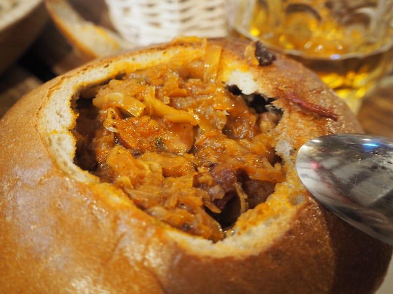 """... bietet polnische Klassiker, wie diese """"Krautfleischsuppe"""", die direkt im Brotwecken serviert wird ..."""