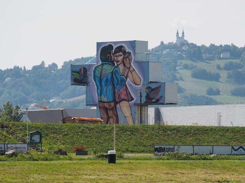 """... und weist auf großflächige Graffitikunst hin, wie sie sonst nirgendwo so in Österreich propagiert wird : """"Only in Linz"""", ein riesiges Graffiti-Kunstwerk mit Blick auf den Pöstlingberg dahinter."""
