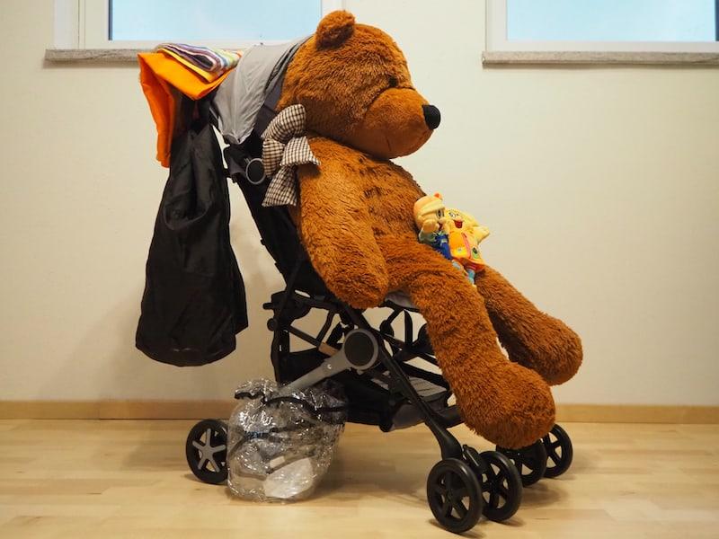Ansicht unseres Reisekinderwagens (mit Riesen-Bär, Spielzeug, Regenschutz, Tragetasche und Tragetüchern für Baby Liam).