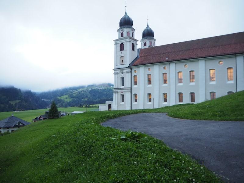 Rund um das Kloster genieße ich bei meinem Morgenspaziergang den Blick auf die Klosterkirche samt den zum Morgengebet hell erleuchteten Fenstern.