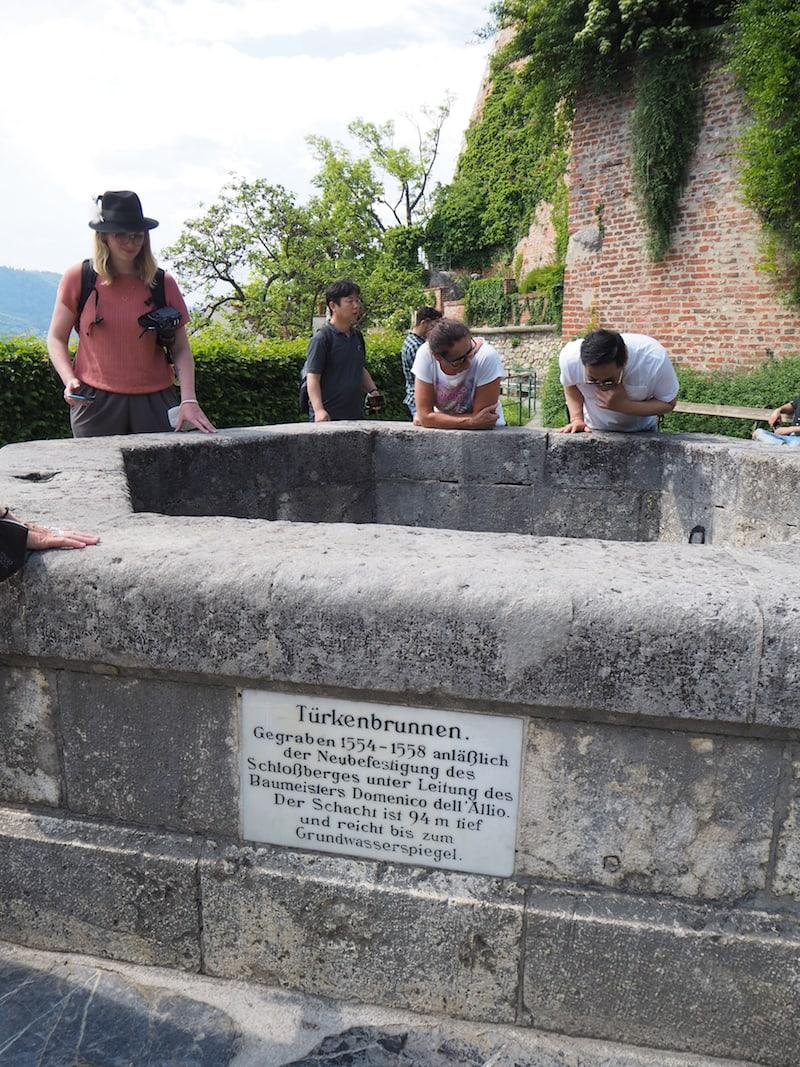 Wasser, das Sigrid Alber demonstrativ in den Türkenbrunnen schüttet, braucht viele Sekunden um anzukommen: Knapp 100 Meter tief ist dieser historische Brunnen auf dem Schlossberg Graz!