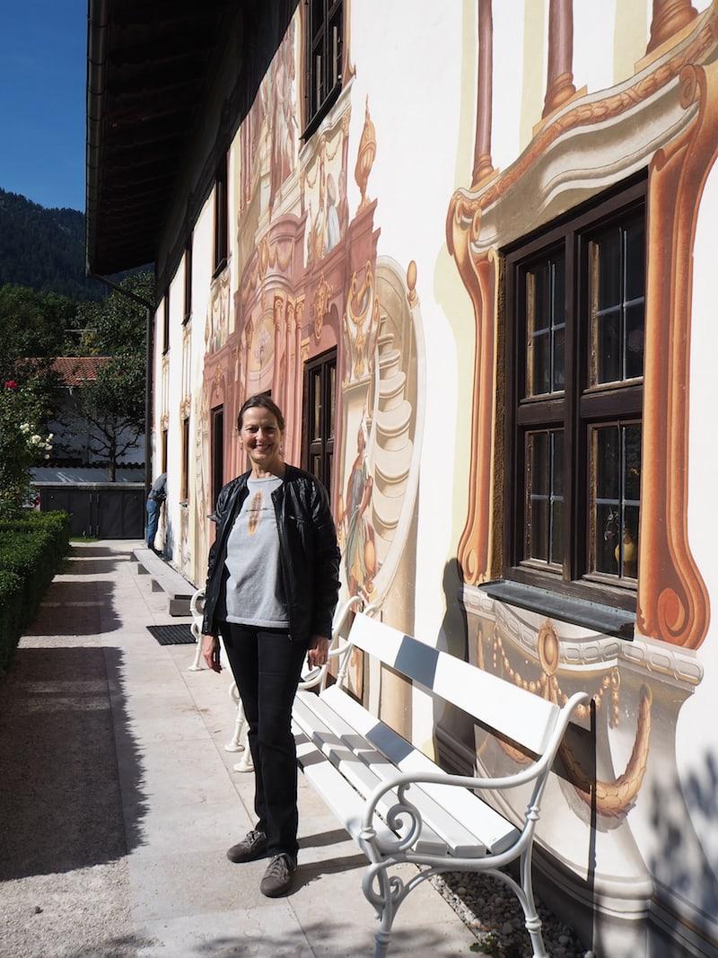 ... meine charmante Ortsführerin ... ist überdies auch Holzbildhauerin: Sie erklärt mir die Geschichte von Oberammergau anhand der berühmten Lüftlmalerei ...